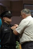 Lt. Ronald Smith Pinning Badge on His Grandson